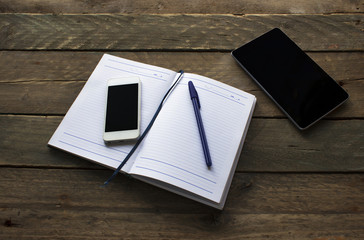 notepad with pen , phone and tablet on wooden table