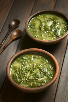 Chard soup with small wooden spoons on the side, photographed on dark wood with natural light (Selective Focus, Focus one third into the first soup)