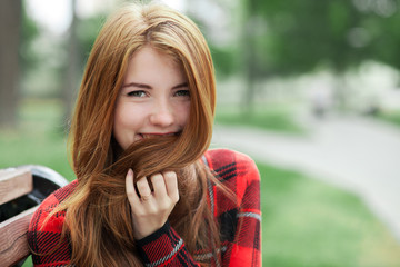 Closeup portrait of young smiling redhead woman in red plaid jacket touching her hair with blurred park background