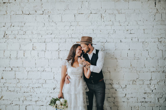 girl with a wreath of white flowers on the head in a white wedding dress and a bearded man in a suit and a hat are holding a bouquet of white flowers and green against a white brick wall