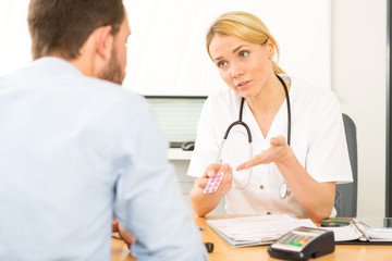 Young attractive woman doctor giving pills to a patient