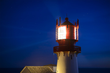 Lighthouse Lindesnes Fyr shines at night on most southern point of Norway, Europe