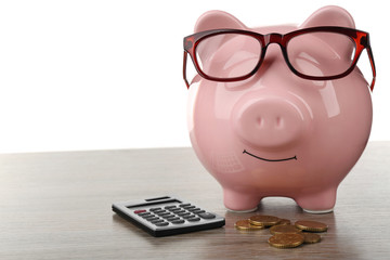 Pink piggy bank with coins, glasses and calculator on white background