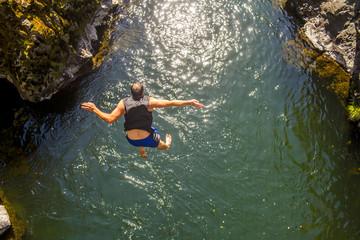 Caucasian man jumping off rocks into ocean
