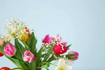 Bouquet of beautiful colorful tulips on light blue wall background