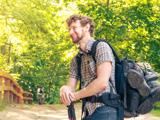 young man with backpack hiking in forest trail