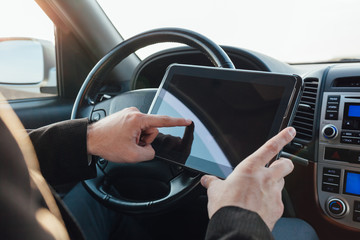 Driver adjusts the navigation on tablet