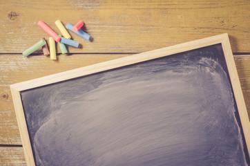 Dark wiped chalkboard on wooden background