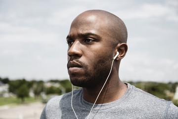 Black runner listening to earbuds