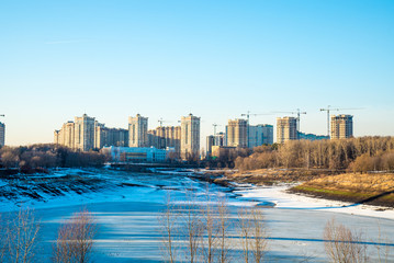 Residential buildings in winter with snow, park and city skyline with skyscrapers, blue sky.
