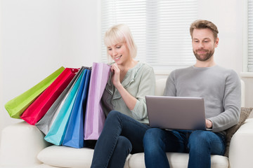 Young Couple With Shopping Bags And Laptop
