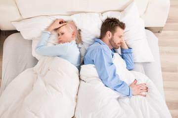 Sad Couple Lying On Bed