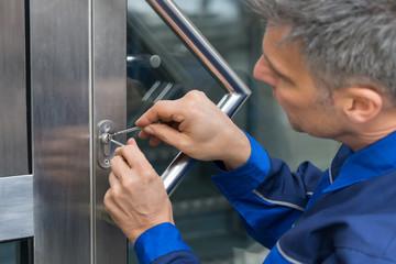 Male Lockpicker Fixing Door Handle At Home Wall mural