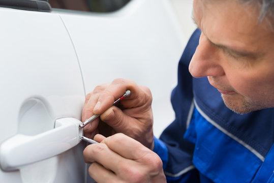 Hand Holding Lockpicker To Open Car Door