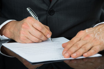 Close-up Of Businessman Hand Holding Pen Over Contract Form
