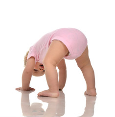 Infant child baby girl in diaper standing upside down on head in