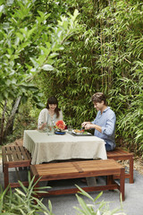 Caucasian couple eating at table outdoors