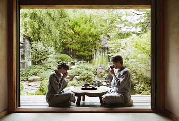 Caucasian couple in robes drinking tea in zen garden
