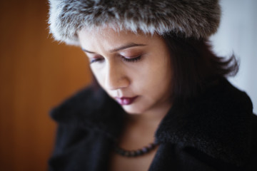 Mixed race woman wearing furry hat and coat