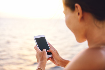 Smartphone woman texting on social media app looking at display screen for sms reading on ocean background on a sea cruise balcony or beach at sunset on holiday. Unrecognizable girl using smart phone.
