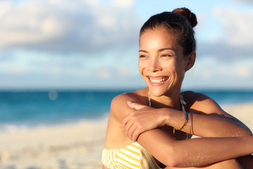 Happy healthy young Asian chinese woman smiling on beach enjoying relax lifestyle sitting in swimwear. Beautiful mixed race tourist in hair bun and golden jewelry at sunset on Caribbean travel.