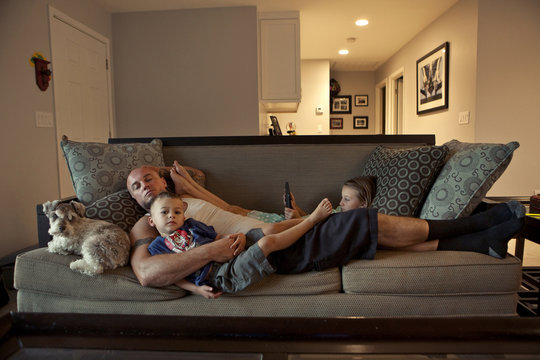 Caucasian father and children relaxing on sofa