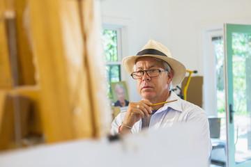 Older Hispanic artist painting in studio