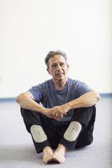 Senior Caucasian man sitting on floor