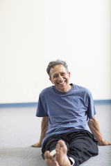Senior Caucasian man smiling on floor