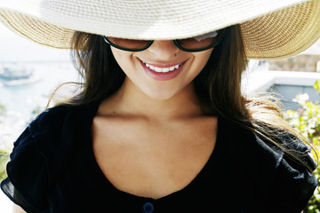 Smiling mixed race woman wearing sunglasses and sun hat