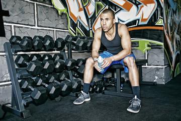 African American man resting in gym