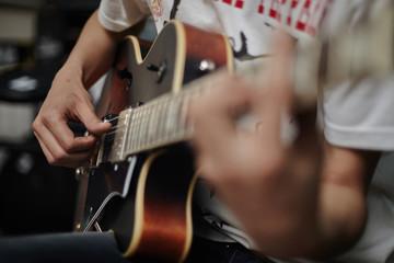 Close up of Caucasian man playing guitar