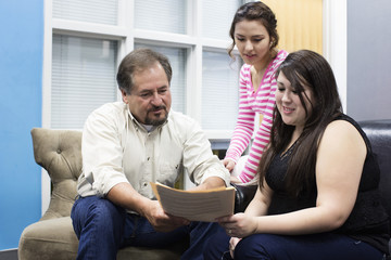 Hispanic teacher and students reading in campus lounge
