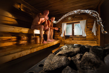 Middle aged couple in traditional wooden Finnish sauna