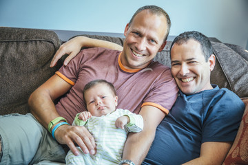 Caucasian gay couple smiling with baby boy on sofa