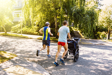 Caucasian gay couple jogging with stroller in neighborhood