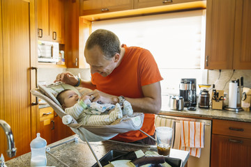 Caucasian father playing with baby boy in kitchen