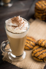 Glass of coffee with cookies on wooden background. Shallow depth of field.