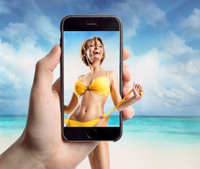 Woman on the beach in a mobile phone
