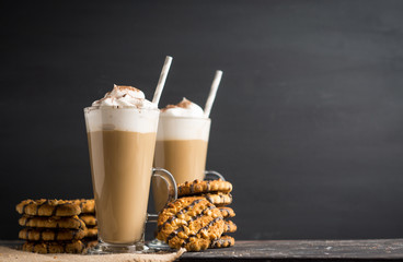 Glass of coffee with cookies on wooden background