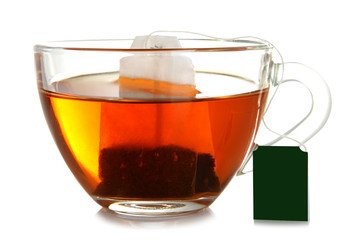 a bag of brewed green tea in transparent Cup on white isolated background