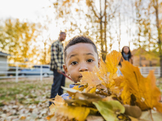 Black boy holding bundle of autumn leaves
