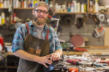 Caucasian craftsman smiling in workshop