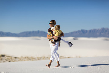 Caucasian mother carrying son on sand dune