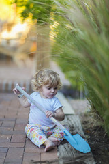 Caucasian boy playing with spade in garden