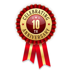 Gold 10th anniversary badge, rosette with red ribbon on white background