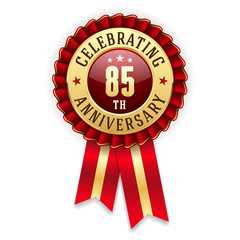 Gold 85th anniversary badge, rosette with red ribbon on white background