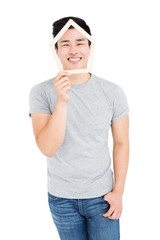 Young man holding house shaped popsicle sticks on face