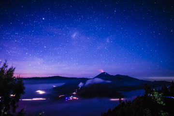 Starry night sky over active volcano