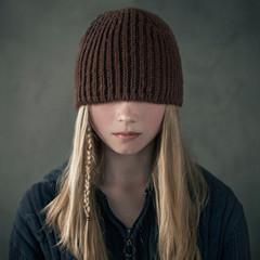 Teenage girl wearing knitted cap over eyes